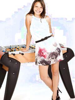 Девушка с веснушками извивается возле футбольного стола