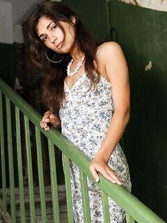 Молодая худышка с темными волосами обнажилась на лестничной площадке