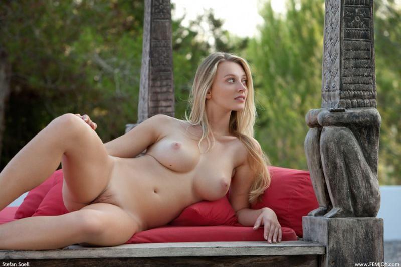 Модель с большими дойками лежит на кровати во дворе