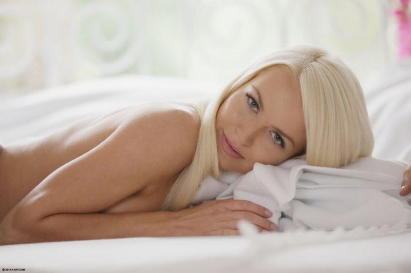 Блондинка сняла на кровати кружевные трусики и любуется киской