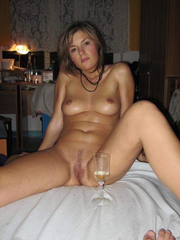 Голая мамзель попивает шампанское на кровати