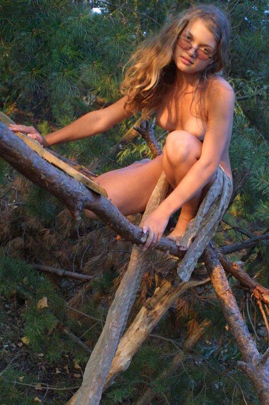 Сельская красотка позирует нагая в лесу