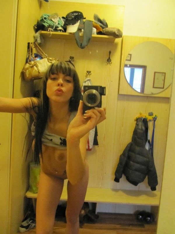 Милая брюнетка с татуировкой на животе делает селфи перед зеркалом