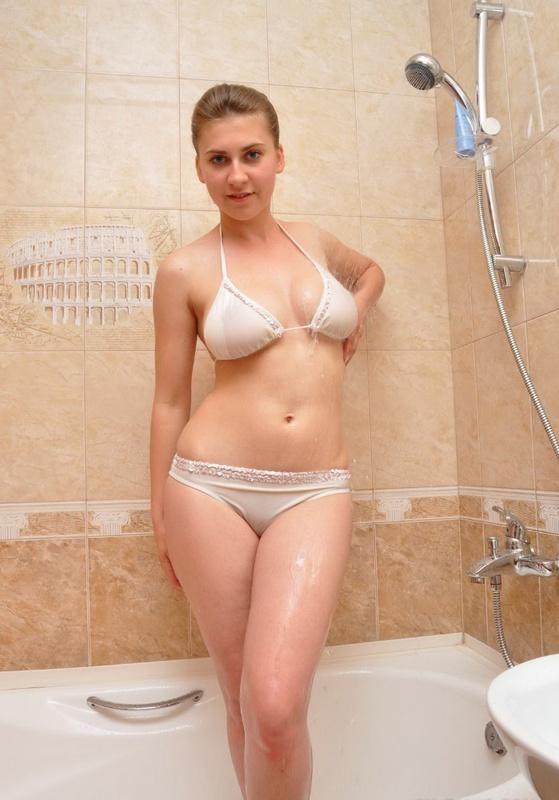 Деваха в белом белье позирует в ванной и раздевается