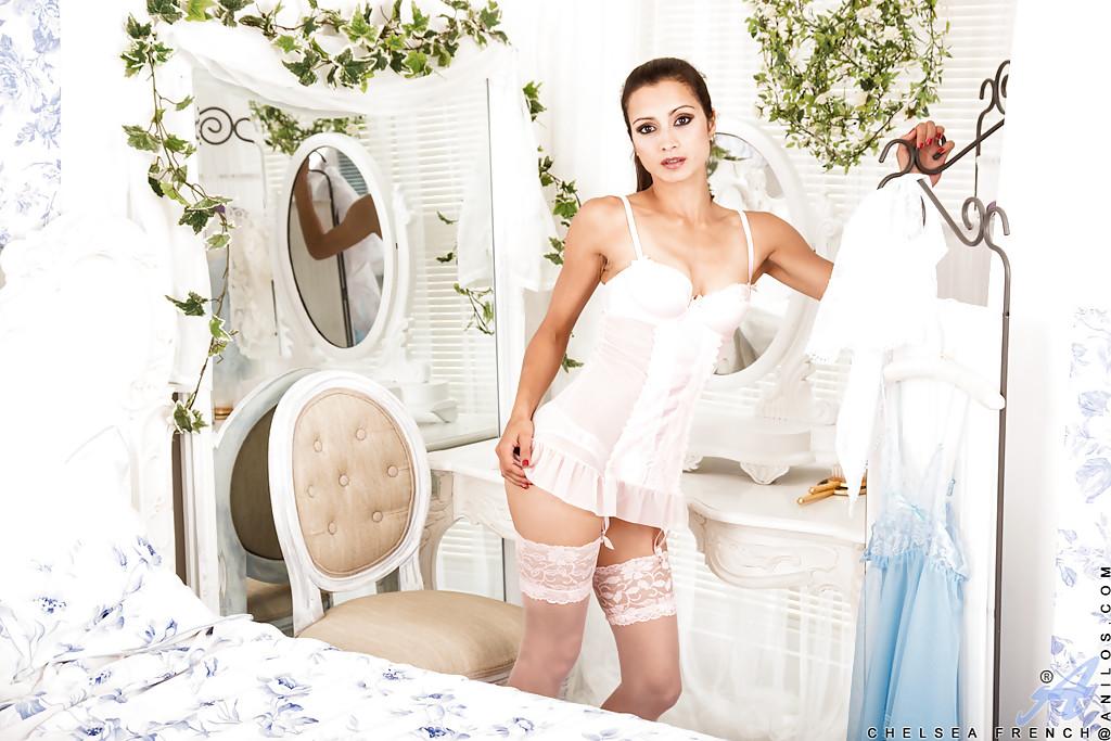 Симпатичная крошка в белом белье позирует на кровати