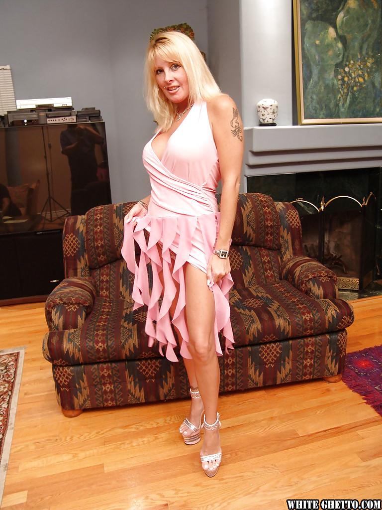 Зрелая блондинка с большими дойками раздевается на диване