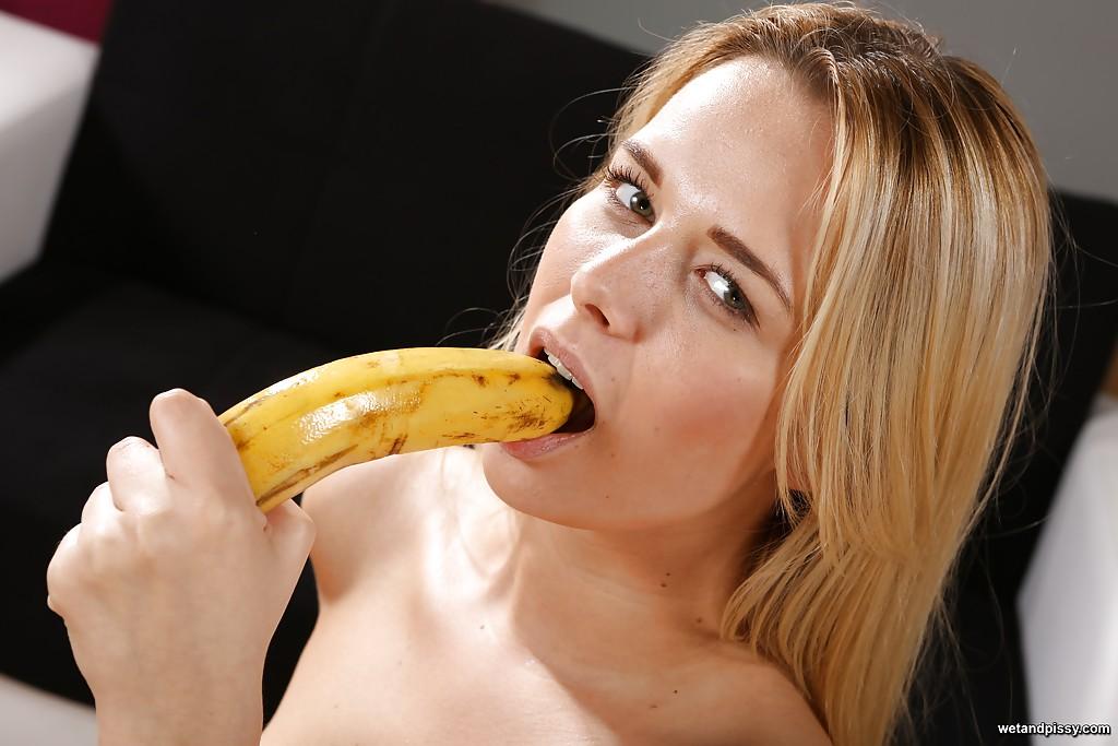 Игривая блондинка ласкает пилотку бананом на столе