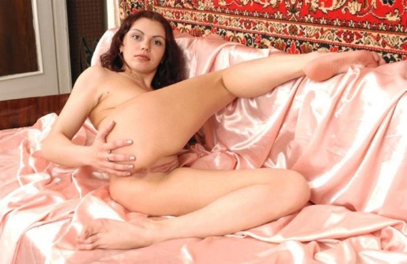 Обнаженная леди позирует на кровати на фоне ковра
