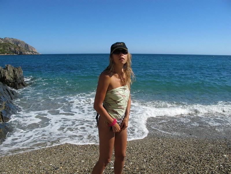Голая дама загорает на пляже выложив на ракушки на тело