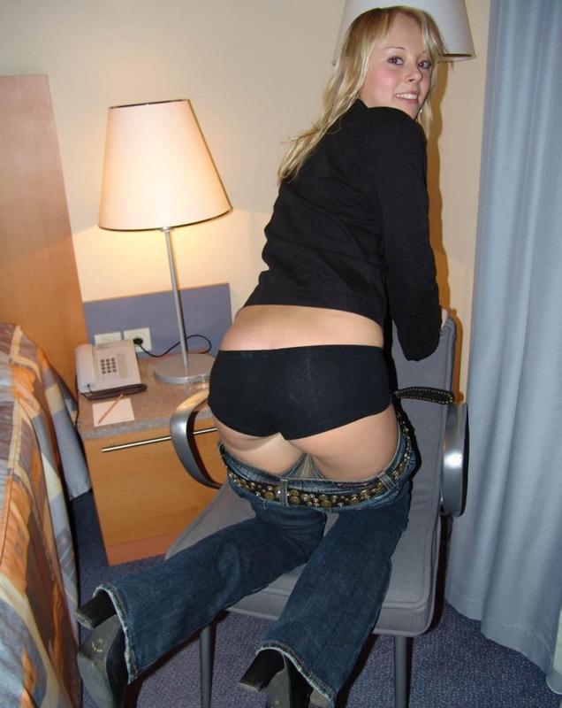 Белокурая любовница раздевается в номере отеля на кровати