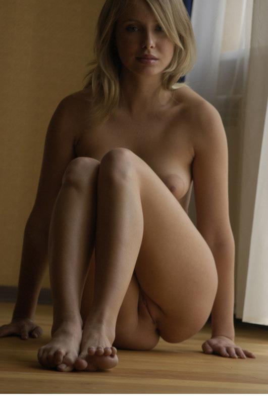 Голая блондинка показывает киску, извиваясь на полу