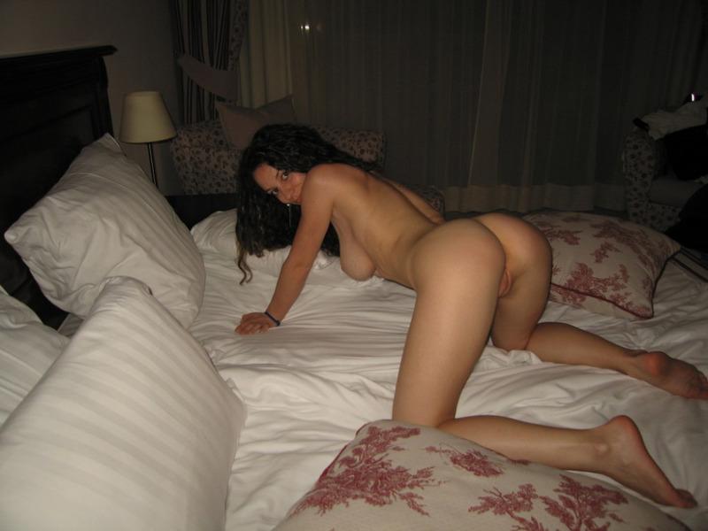 Кучерявая милфа тискает себя за дойки на большой кровати