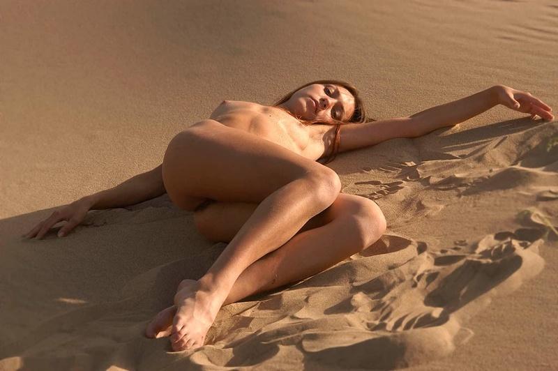 Молодуха с интимной стрижкой позирует голой на песке