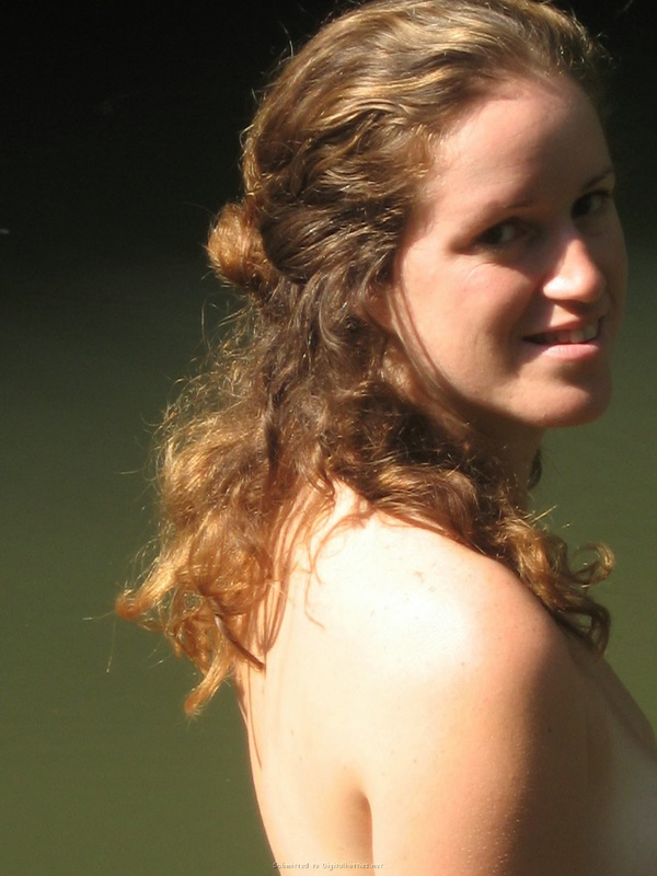 Симпатичная молодуха в дикой природе светит обнаженным телом возле реки