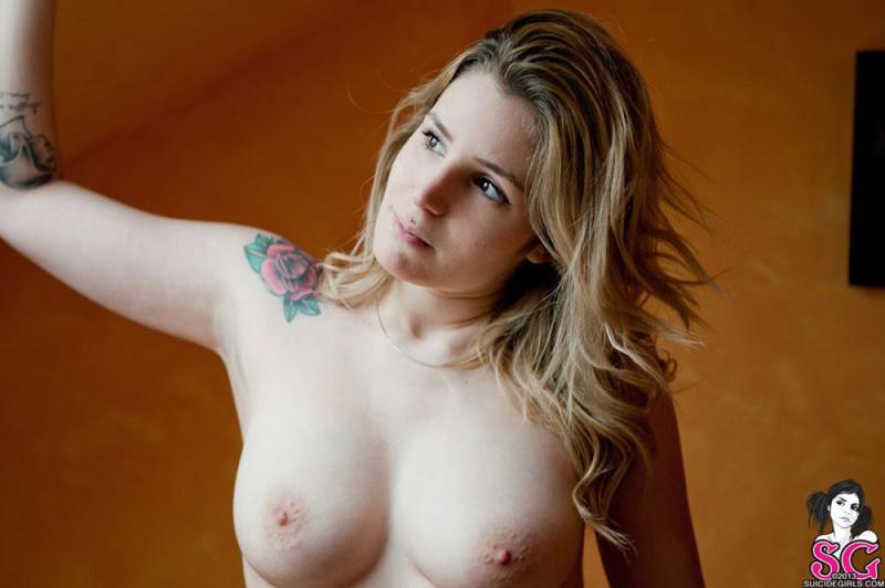 Татуированная красотка с большой попкой светит обнаженным телом на кровати