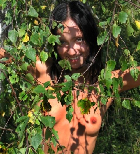 Стройная брюнетка залезла голой на дерево